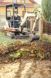 Mini excavator on construction site. Excavator regulates the terrain around the house. Digger digging soil.  stock photo