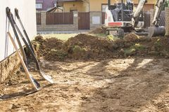 Mini excavator on construction site. Excavator regulates the terrain around the house. Digger digging soil with shovels. In foreground stock image