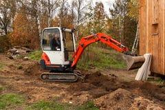 Mini excavator on construction site. Excavator regulates the terrain around the house. Royalty Free Stock Photography