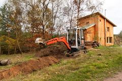 Mini excavator on construction site. Construction of a family house near a forest. Stock Image