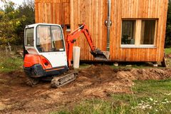 Mini excavator on construction site. Excavator regulates the terrain around the house. Mini excavator on construction site. Excavator regulates the terrain royalty free stock photography