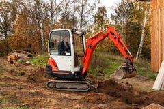 Mini excavator on construction site. Excavator regulates the terrain around the house. Stock Image