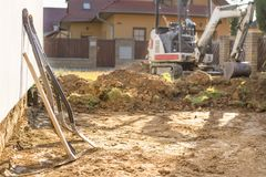 Mini excavator on construction site. Excavator regulates the terrain around the house. Digger digging soil with shovels. In foreground royalty free stock photos