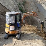 Mini excavator. Digging earth at construction site stock photos