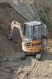 Mini digger excavator. Mini excavator digging earth at construction site royalty free stock photos
