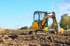 Mini excavator JCB 8025 ZTS digging earth in a field or forest