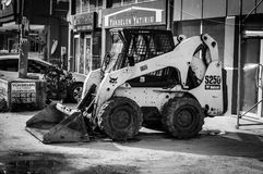Mini Backhoe Excavator Loader In Side Street. Mini excavator loader in a side street for urban renewal projects in progress in order to create build more rugged Royalty Free Stock Photos
