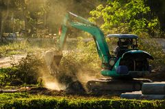 Mini EXCAVATOR. Working on dusty soil royalty free stock images