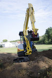 Mini-Excavator. Pushing Dirt and digging Royalty Free Stock Photo