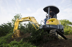 Mini-Excavator. Pushing Dirt and digging Stock Image