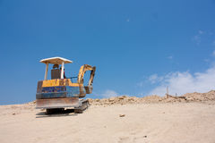 Mini excavator working. On earht mountain Stock Photography