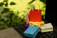 Mini- färgrika pappers- shoppingpåsar på bärbar datortangentbordet Idéabou royaltyfria bilder