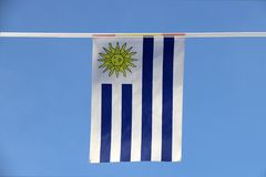 Mini fabric rail flag of Uruguay, It has a field of nine equal horizontal stripes alternating white and blue with symbolic of sun. It hanging on the rope cloth royalty free stock images