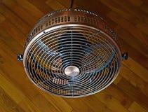 Mini fan portátil de mirada antigua del piso del ventilador en el suelo de entarimado diagonal Foto de archivo libre de regalías