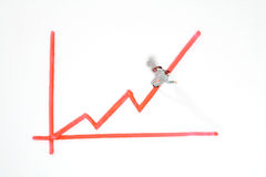 Mini figure climbing ascending graph. Miniature toy figure of a man climbing an ascending line graph conceptual of ambition, achievement and growth Royalty Free Stock Photo