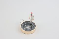 Mini figure standing on a compass Stock Photo