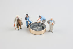 Mini figure standing on a compass Stock Photography
