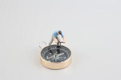 Mini figure standing on a compass Royalty Free Stock Photos