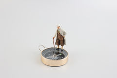 Mini figure standing on a compass Royalty Free Stock Image