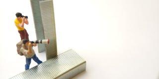 Top View 2 Mini Figure toy photographer take a photo, hiding at strapler on white stock image