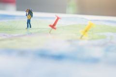 Mini figure traveler with red pushpin and a map travel concept.  Royalty Free Stock Photos