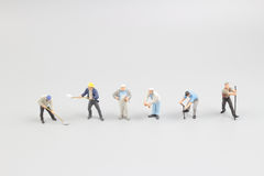 The mini figures of male workers talking. At board royalty free stock image