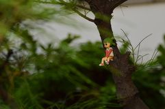 Mini figures sitting on the tree trunks. royalty free stock photography