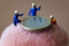 Mini figures and euro coin. Mini figures working and euro coin Stock Images