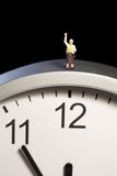 Mini figurine on a clock Stock Photography
