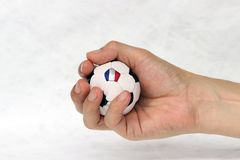 Mini football in hand and one black point of football is France flag on white background. Concept of sport or the game in handle royalty free stock photography