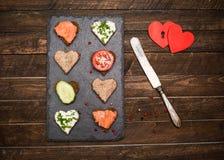 Mini forma do coração dos canapes com coberturas diferentes na ardósia preta Imagens de Stock Royalty Free