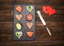 Mini forma do coração dos canapes com coberturas diferentes na ardósia preta Fotografia de Stock Royalty Free