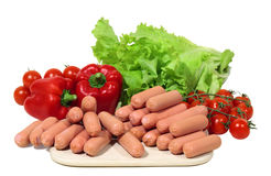 Mini frankfurters. With paprika, tomatos and green salad are waiting for homemakers Royalty Free Stock Images