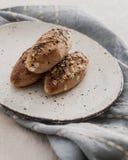 Mini- franska bagetter med linfrö på en blå linne Arkivbilder