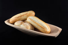 Mini French Baguettes on a rectangular wood bowl with black back Stock Photos
