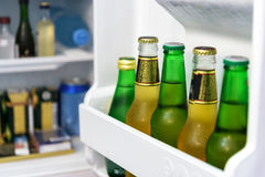 Mini fridge full of bottles in a hotel room. Mini fridge full of bottles of beer, juice and water in a hotel room Royalty Free Stock Images