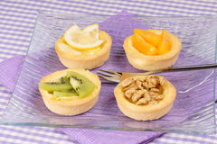 Mini fruit tarts. Close-up of some mini fruit tarts served on a glass plate with dessert fork. Selective focus Stock Images