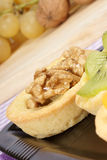 Mini fruit tarts. Close-up of some mini fruit tarts served on a black plate. Selective focus royalty free stock image