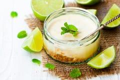 Mini gâteau au fromage de chaux dans un pot en verre sur le fond en bois blanc Images libres de droits