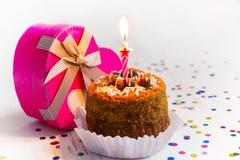 Mini gâteau avec une bougie et un cadeau dans une boîte dans la forme Image libre de droits