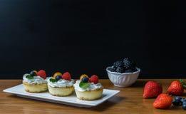Mini gâteaux au fromage avec la fraise et la crème fouettée d'un plat Image stock