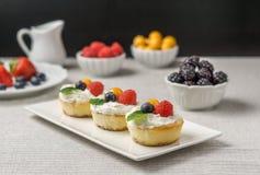 Mini gâteaux au fromage avec la fraise et la crème fouettée d'un plat Photo libre de droits