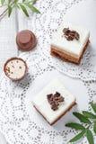 Mini gâteaux avec du chocolat, le cacao et les sucreries blancs sur la fin légère de fond  Photos stock