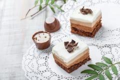 Mini gâteaux avec du chocolat, le cacao et les sucreries blancs sur la fin légère de fond  Images libres de droits