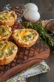 Mini galdérias saborosos das quiche em uma placa de madeira Tortas flocosos da massa Fotos de Stock