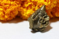 Mini Ganesha made from brass with yellow marigold flower and white background. Mini Ganesha made from brass with yellow marigold flower and white background stock images