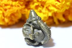 Mini Ganesha made from brass with yellow marigold flower and white background. Mini Ganesha made from brass with yellow marigold flower and white background royalty free stock image