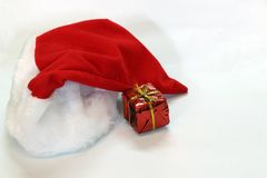 Mini gift box in red reflect gift wrap with golden rope knot and red white christmas hat isolated on white background. It is a thing given willingly to someone stock photography