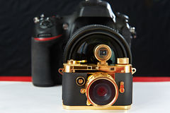 Mini gift golden camera on background of big one Royalty Free Stock Images