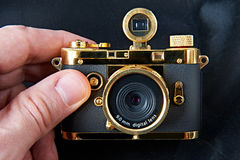 Mini gift golden camera in big hand Stock Photos